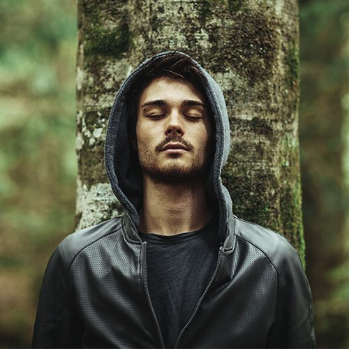 Young man in a forest leaning on a tree with eyes closed